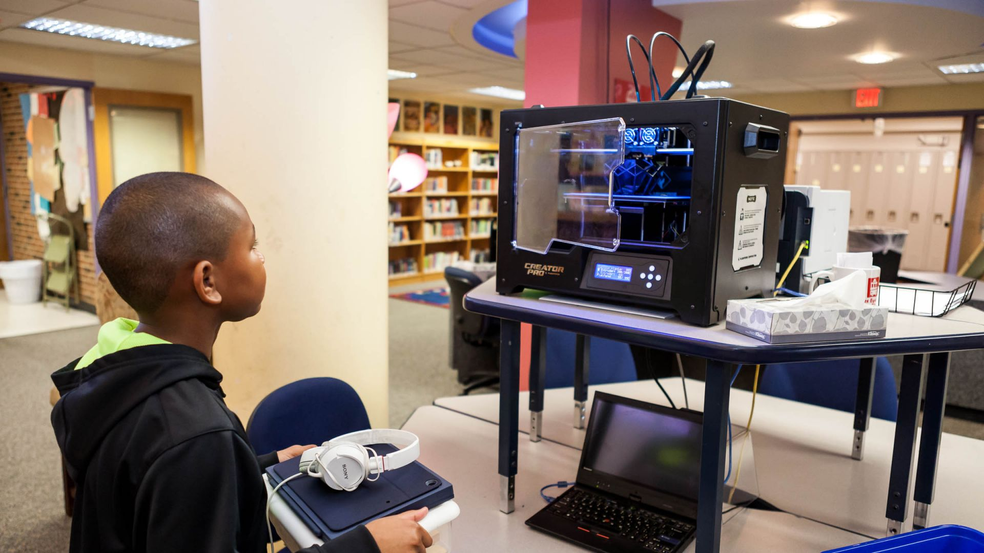 A lower school student watches in amazement as a 3D printer produces a student-designed planter.