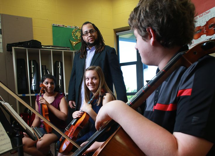 Middle school strings students rehearsing with Mr. Racine.