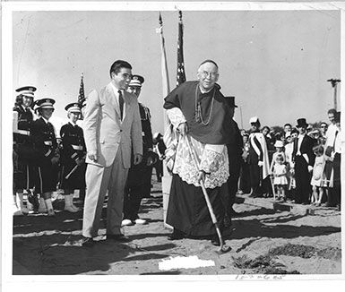 The Central Catholic High School (not yet named Rice Memorial High School) ground-breaking ceremonies were held at the 29-acre site of the new school adjoining the Burlington Country Club off Shelburne Road in South Burlington. Bishop of Burlington, Robert F. Joyce lifted the first shovel of dirt marking the start of the project. At left is Eugene Morrissey, contractor with Wright and Morrissey Construction, along with the Cathedral High School band and the Fourth Degree Knights of Columbus.