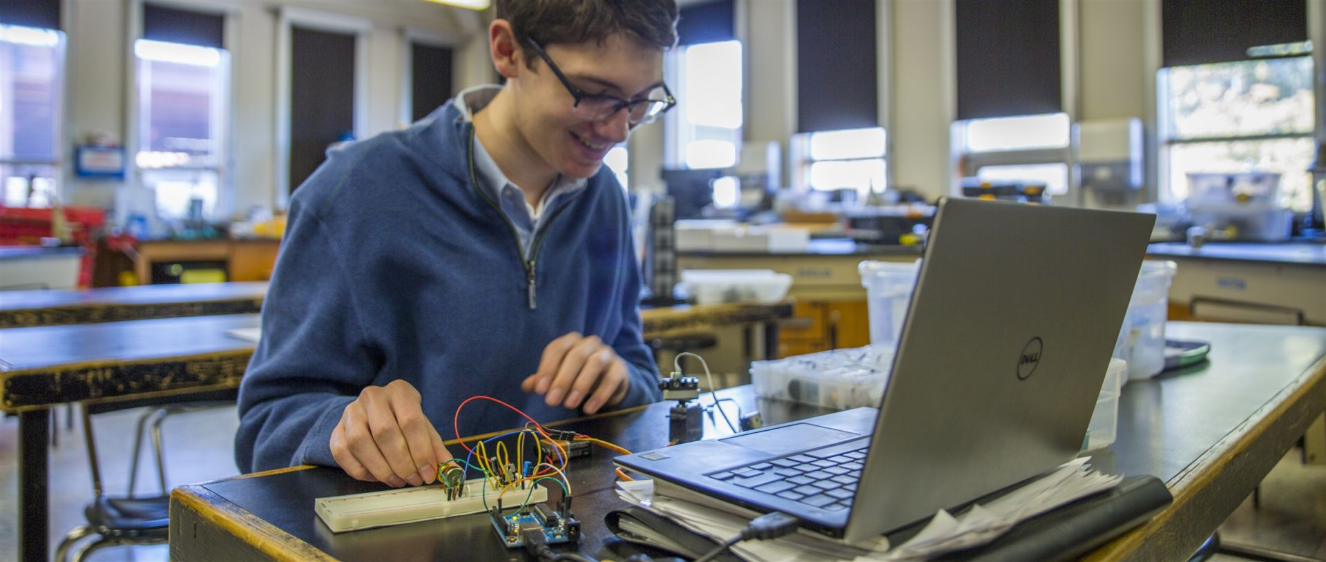 A senior in Information Engineering programs a microcontroller to control a rotating servo motor with a distance sensor attached to it.
