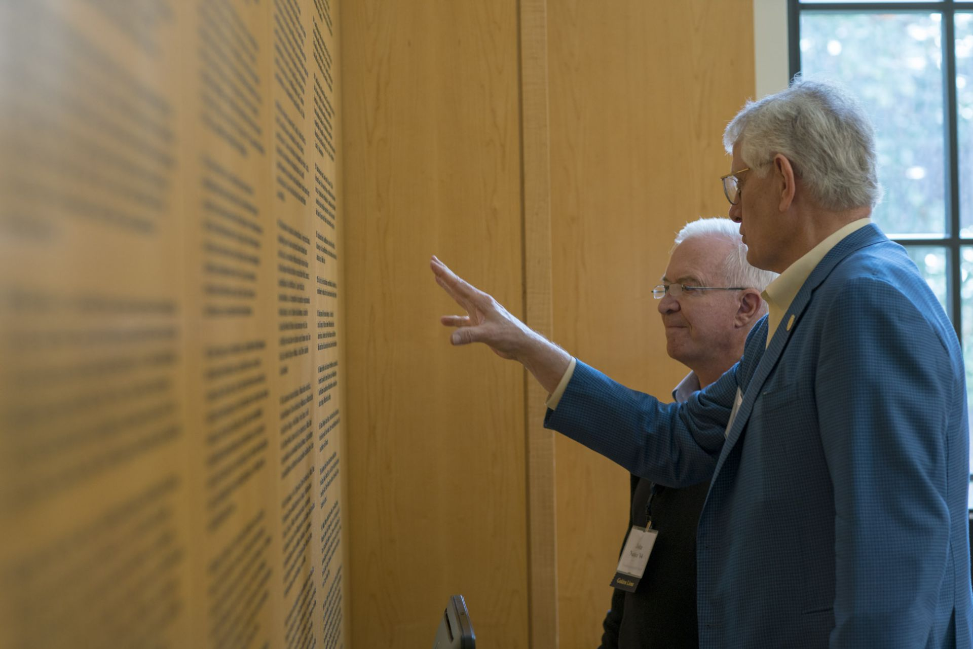 Classmates find their names on the walls of Graduate Hall.