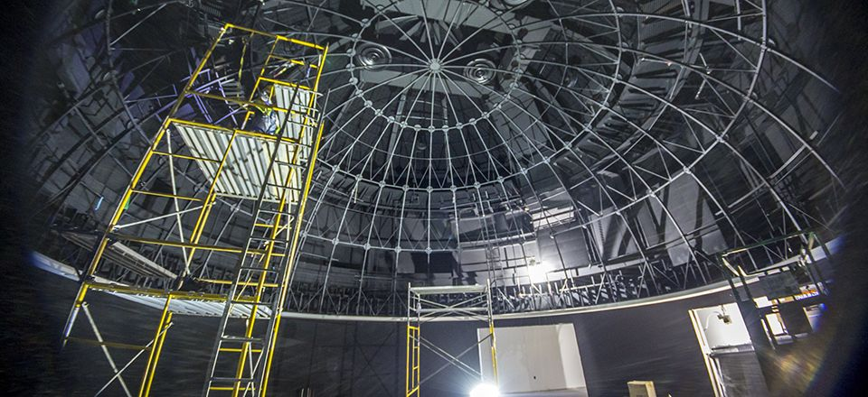 Crews prepare to install the projection dome in the planetarium.