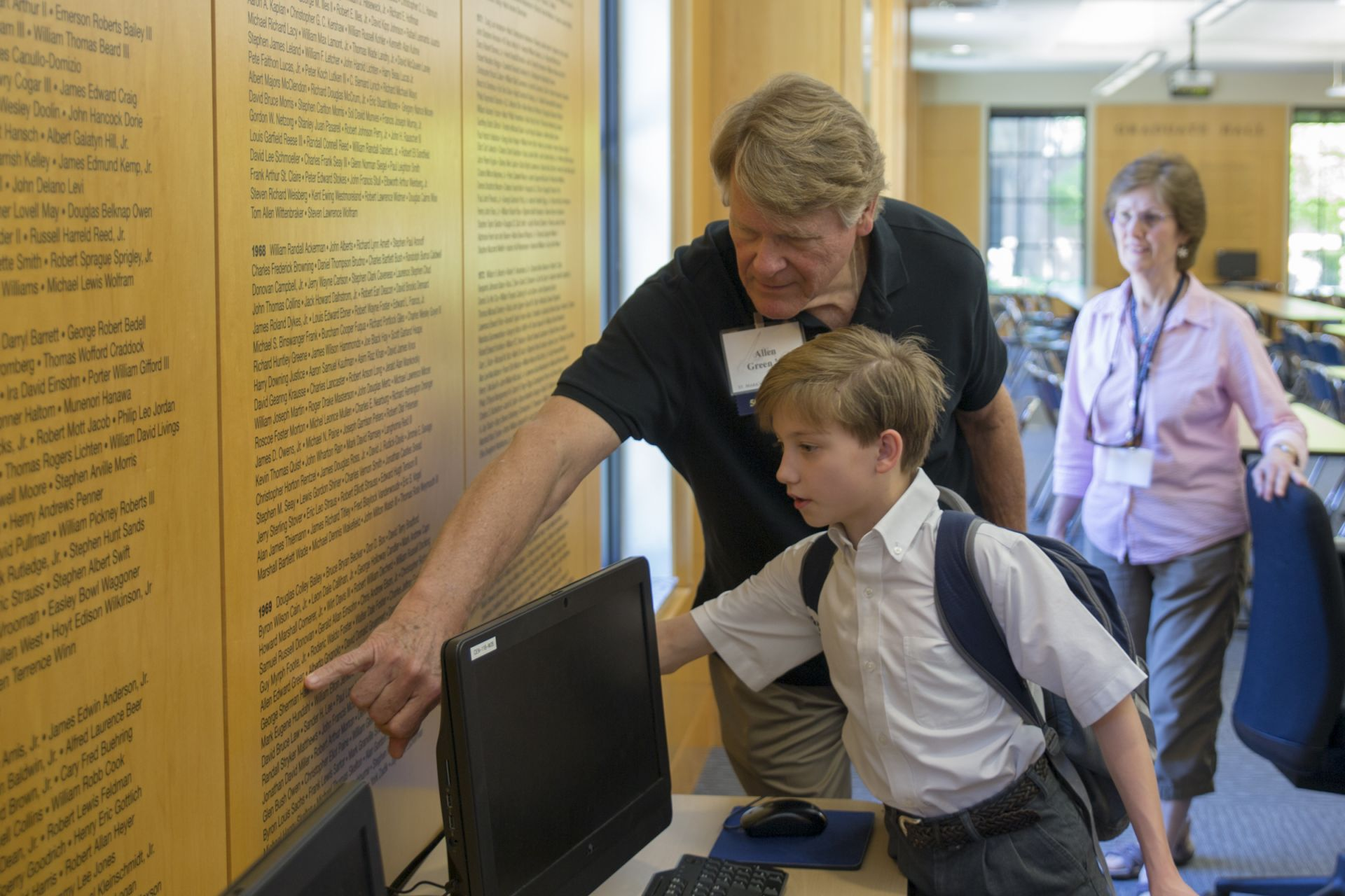 An alumnus shows a student his name in Graduate Hall.