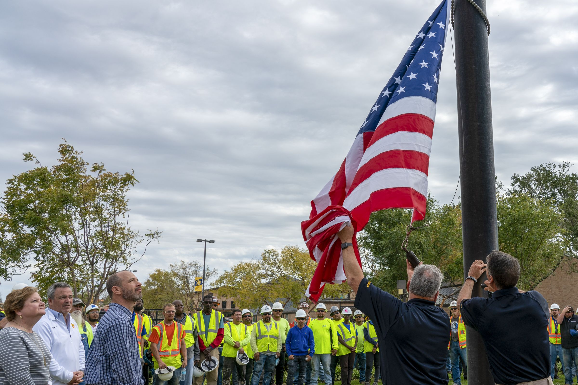 Campus workers and administrators pause to raise the flag on campus for the first time since the tornado struck.