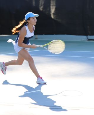 Girls tennis player running toward the net after hitting the ball.