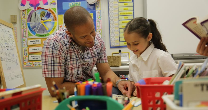 First grade teacher Maurice Adkins works with a student.