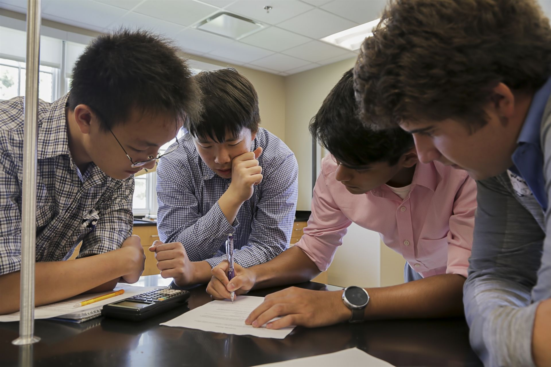Four young men looking over a document at Casady High School in Oklahoma City