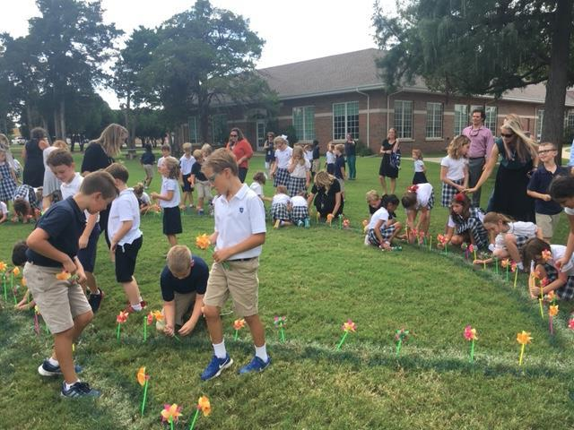 Father Youmans speaks about peace and the wind of the Holy Spirit that brings true peace to the earth. The young Cyclones enjoy placing their pinwheels in the ground on International Day of Peace 2018.