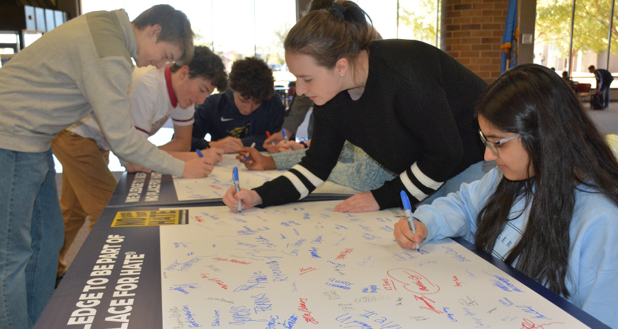 Upper School students sign their names for the