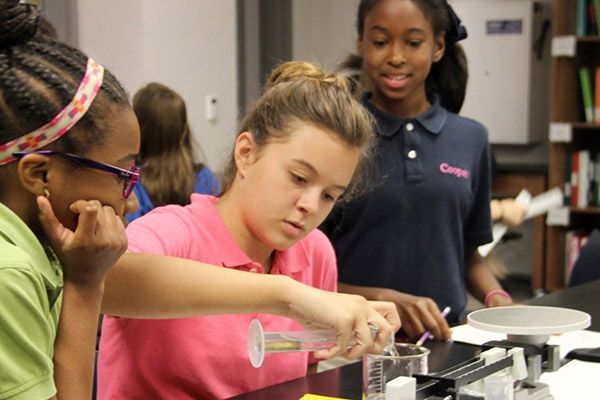 Middle School science students conduct experiment.