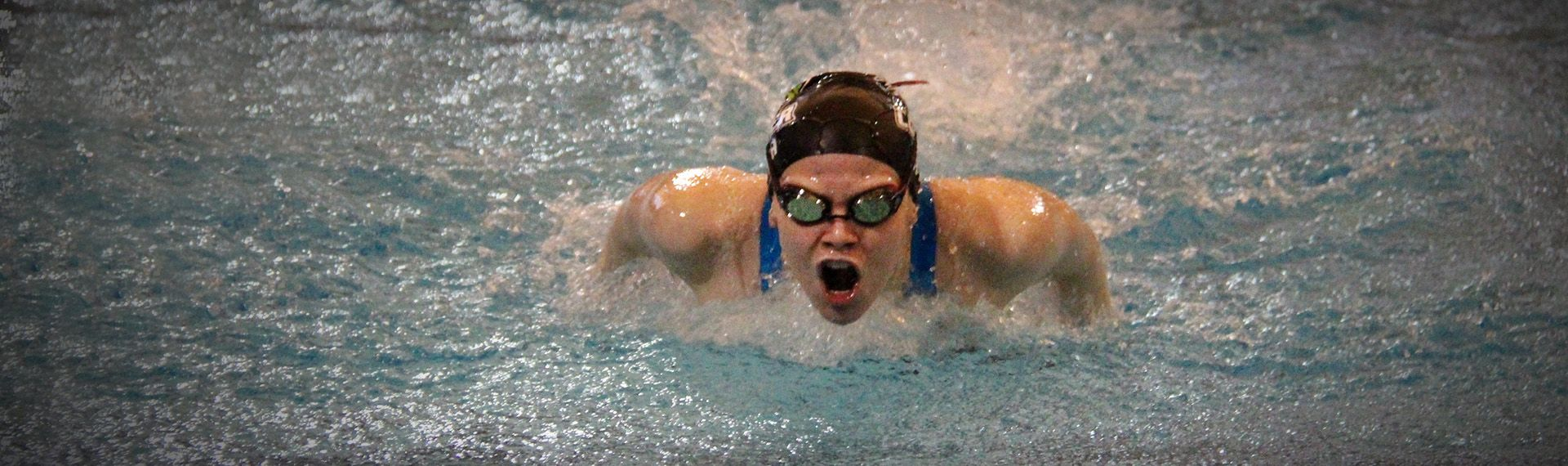 Swimmer takes a breath during butterfly.