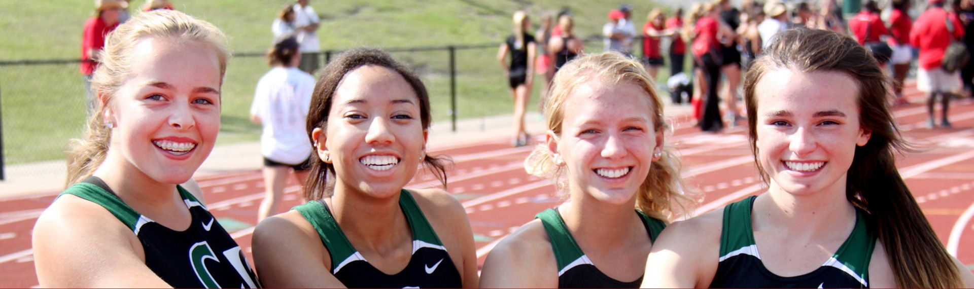 Girls track and field athletes smile at camera.