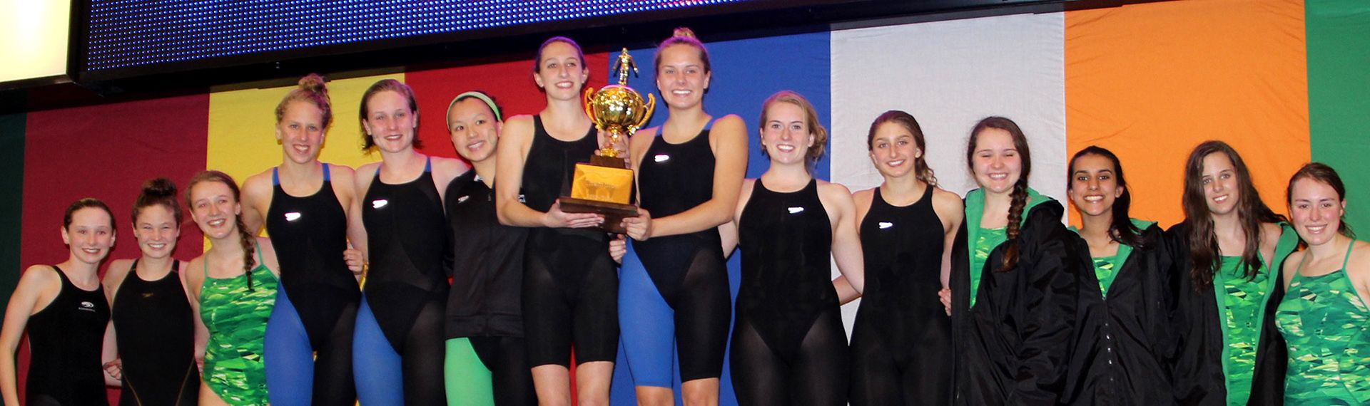 Girl swim team holds championship trophy.