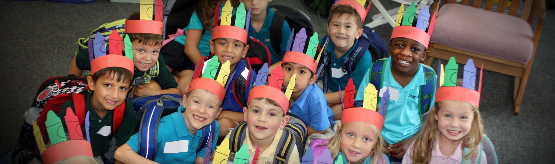 Kindergarden class poses while wearing homemade hats.
