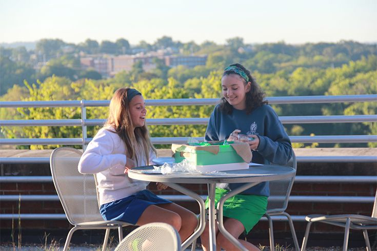 Two GPS girls studying together on patio