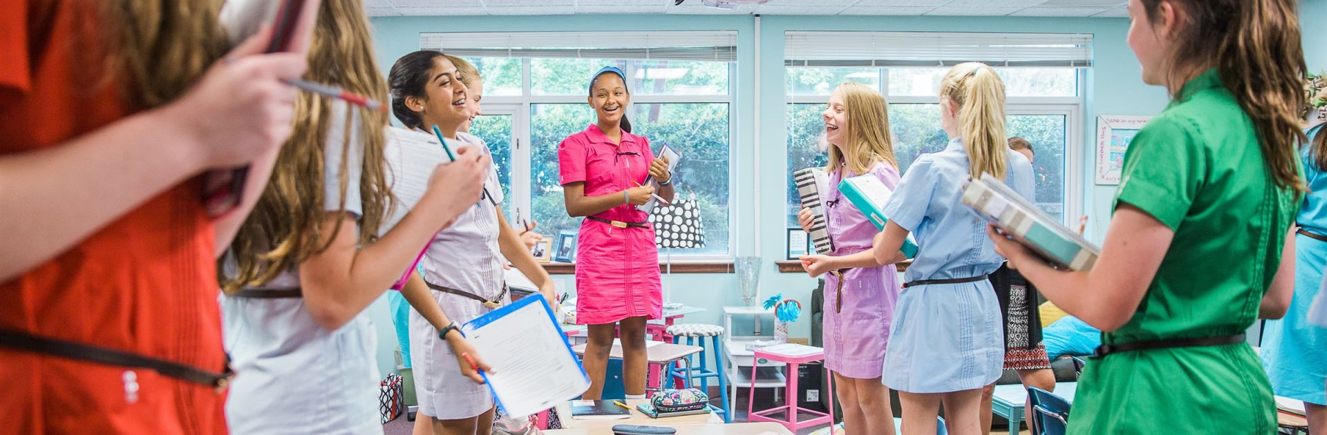 GPS girls stand on chairs in classroom as part of an activity