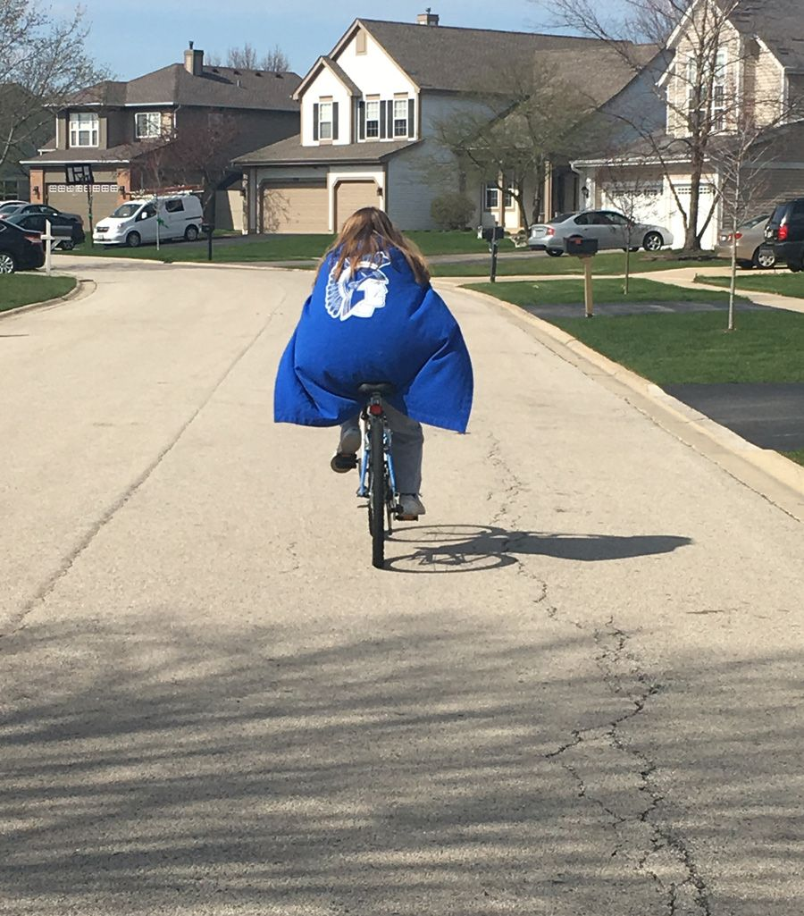 A female student riding a bike with a Spartan cape