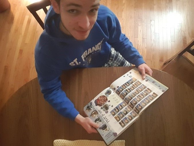 A male student looking at his yearbook at home