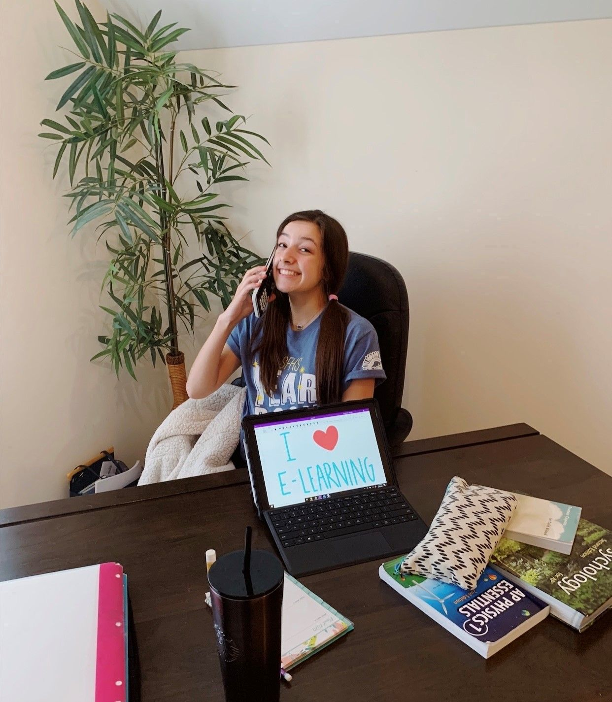 Student  pretending to talk on the phone. Computer has I heart E-Learning
