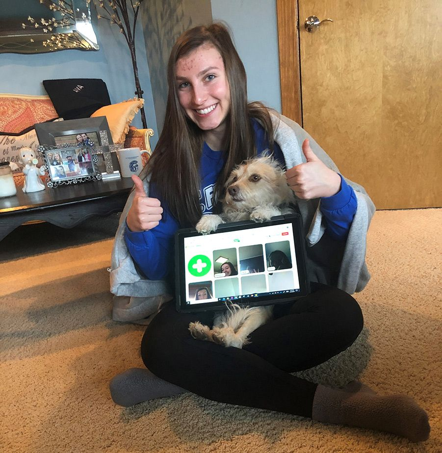 Female student with thumbs up holding a dog and her computer