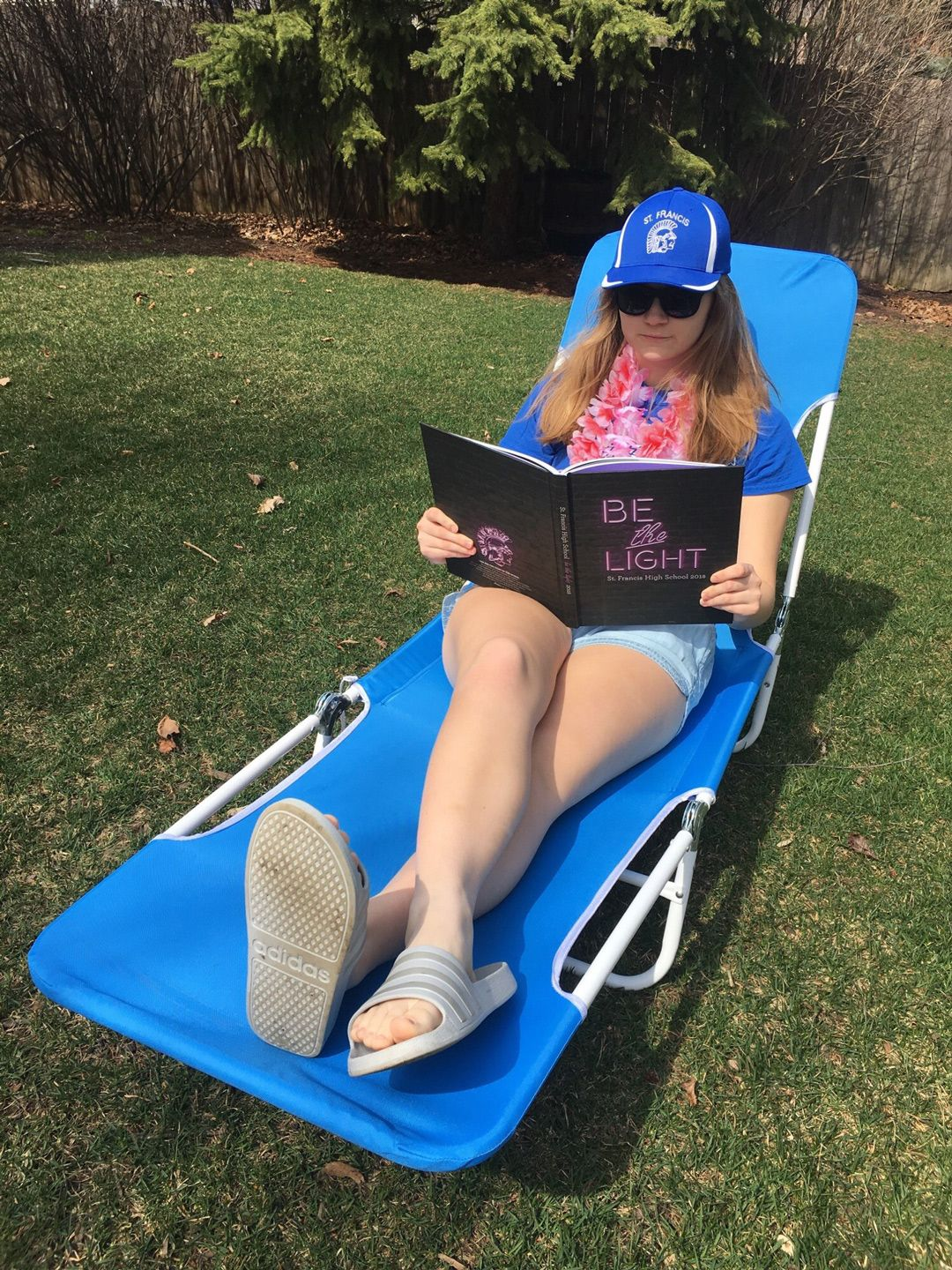 Female student in SFHS spiritwear on a lawnchair reading the yearbook