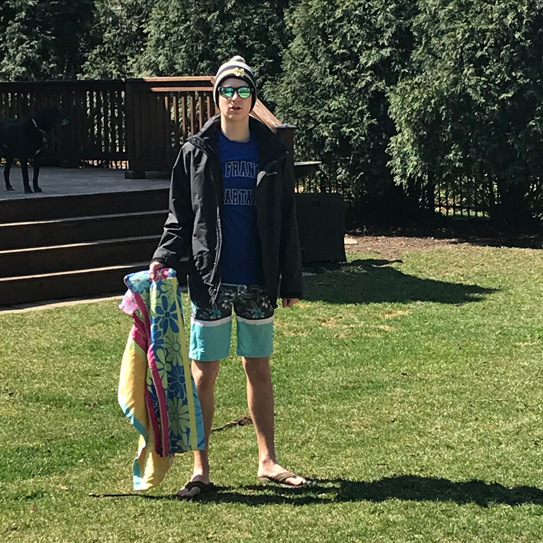 Male student in hat, winter jacket, swim trunks and beach towel