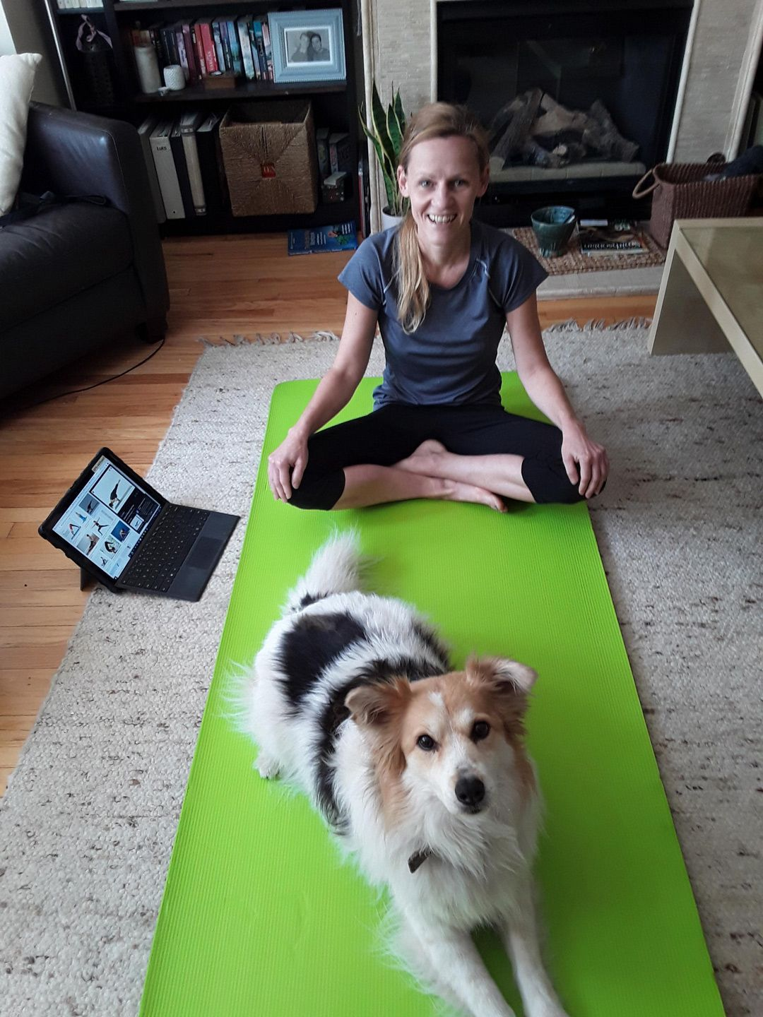 Female teacher with her dog, computer and yoga mat