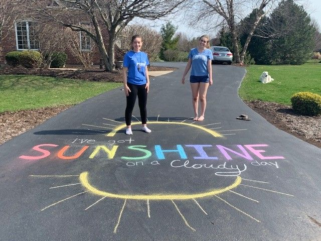 Siblings writing in chalk on their driveway