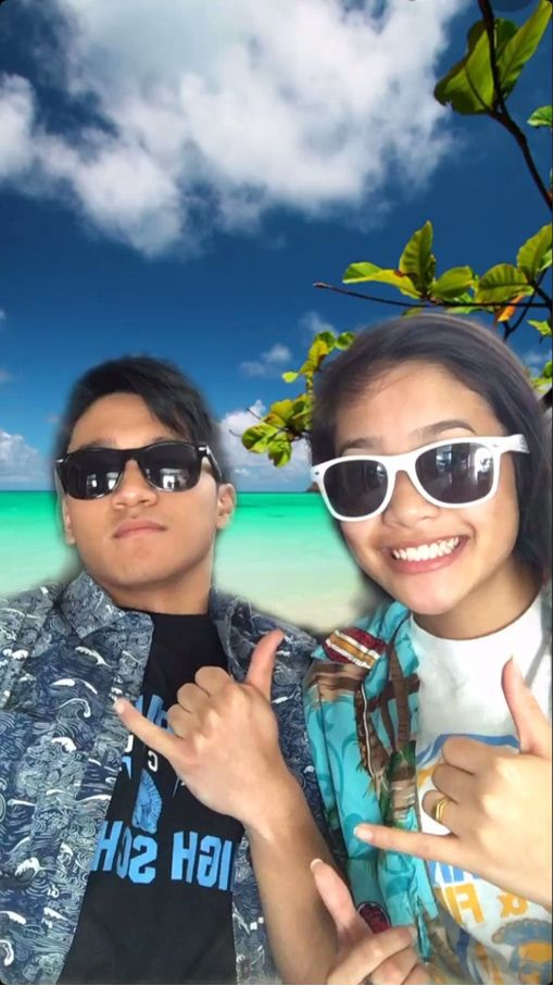 Male and female students in front of a green screen image of a beach