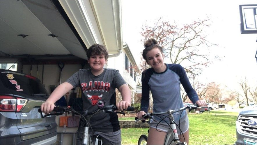 Male and female siblings riding bikes