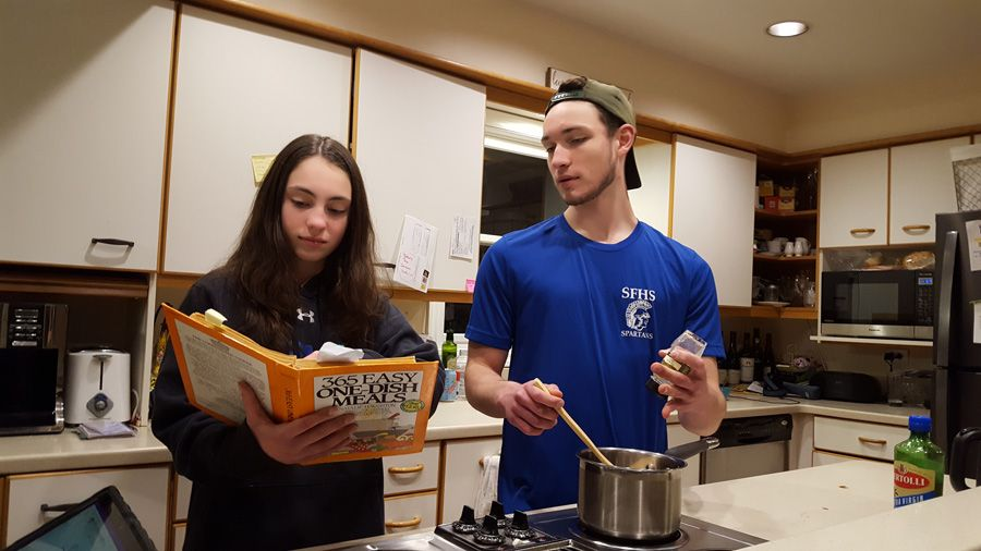 A male and female sibling cooking together