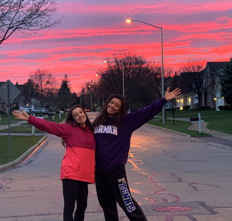 Two female siblings in front of a sunset