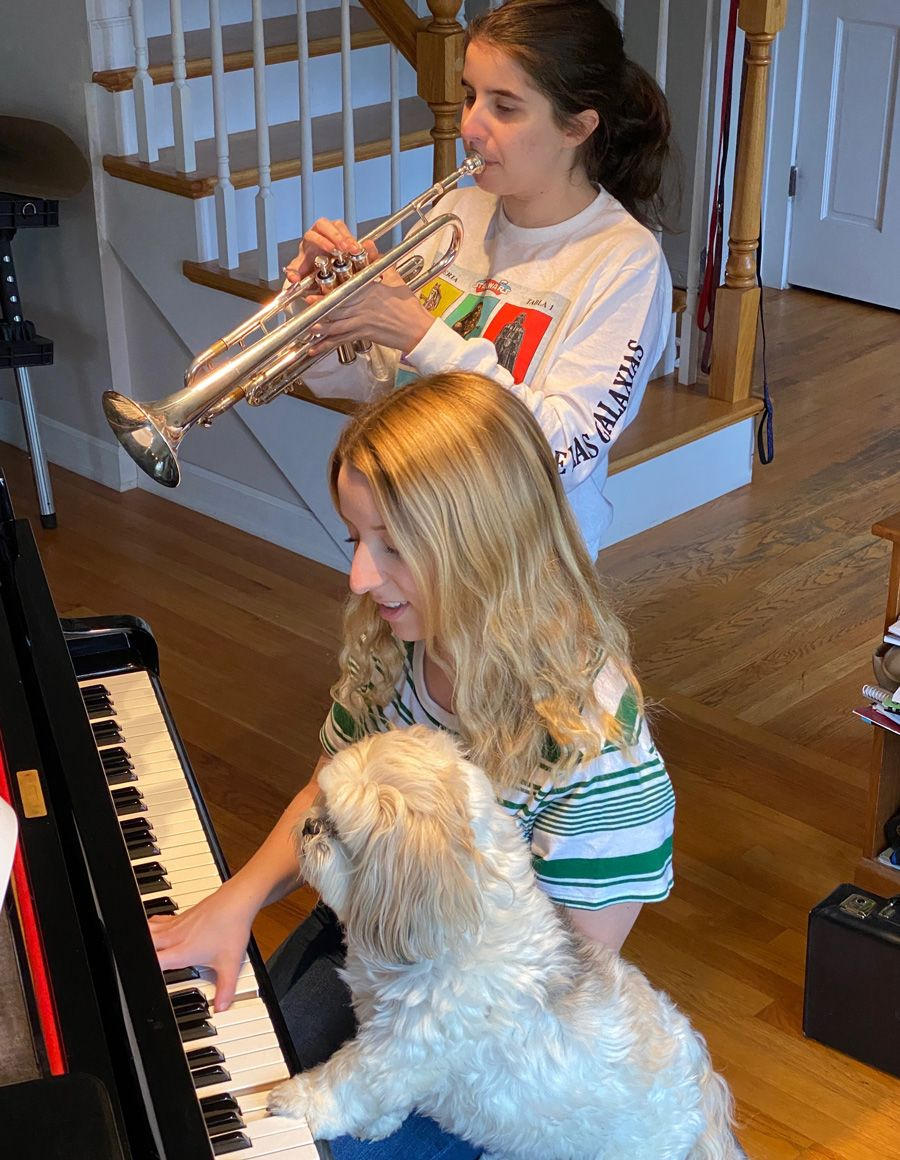 Two female siblings playing the trumpet and piano