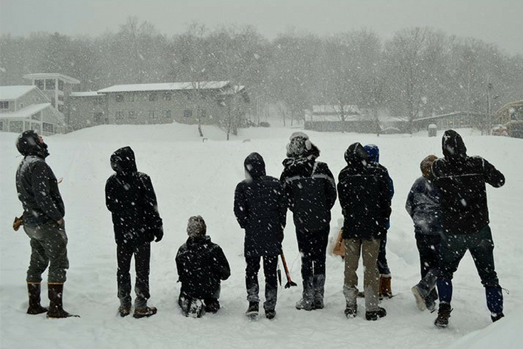 Students measure the arch and angle of a rocket launched in the snow.