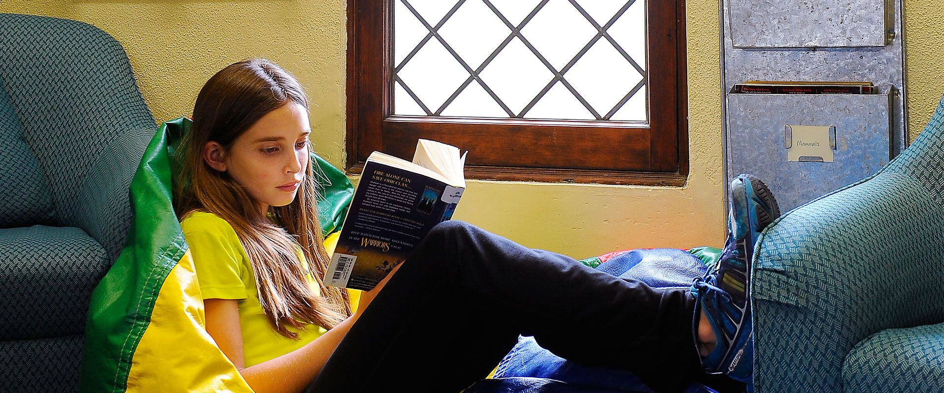 Girl reading book on bean bag chair