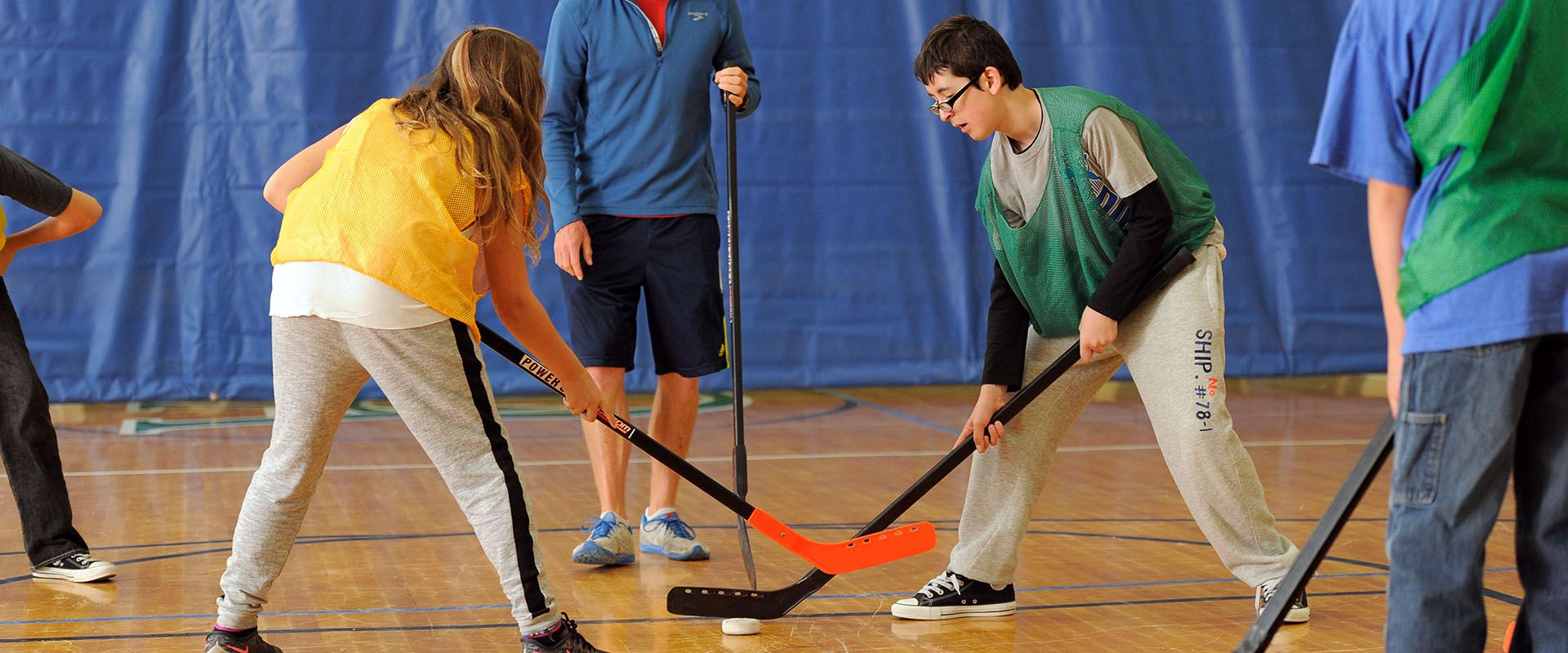 Elementary students playing floor hockey