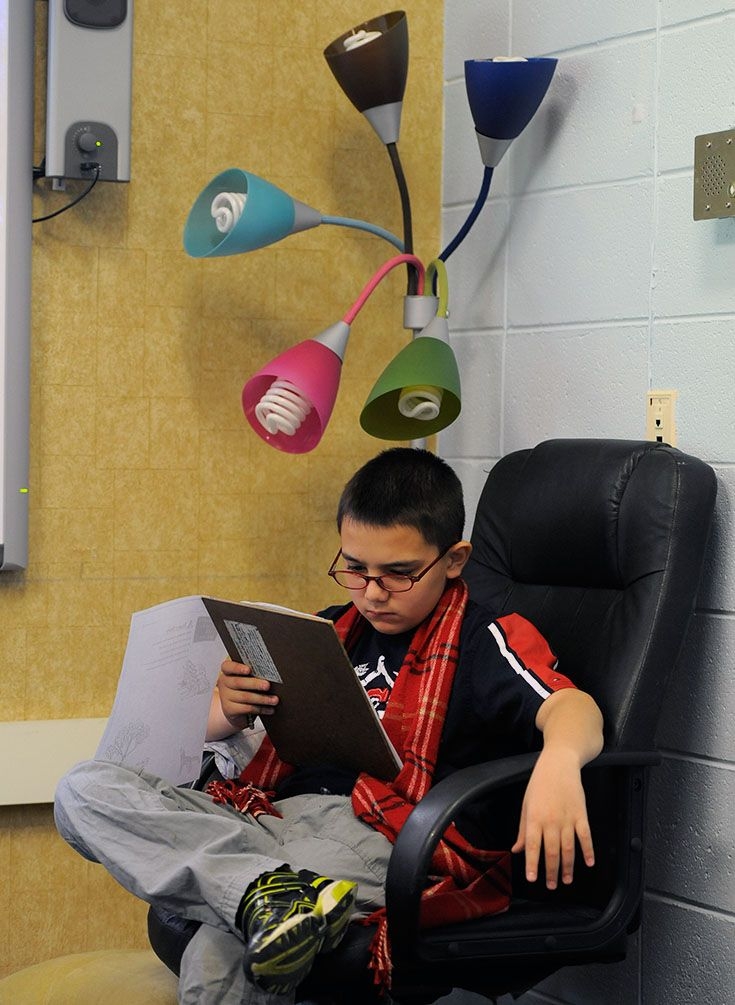 boy reading under a neat lamp