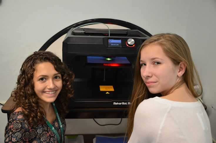 Two students observe the 3D printer as it fabricates one of their creations.