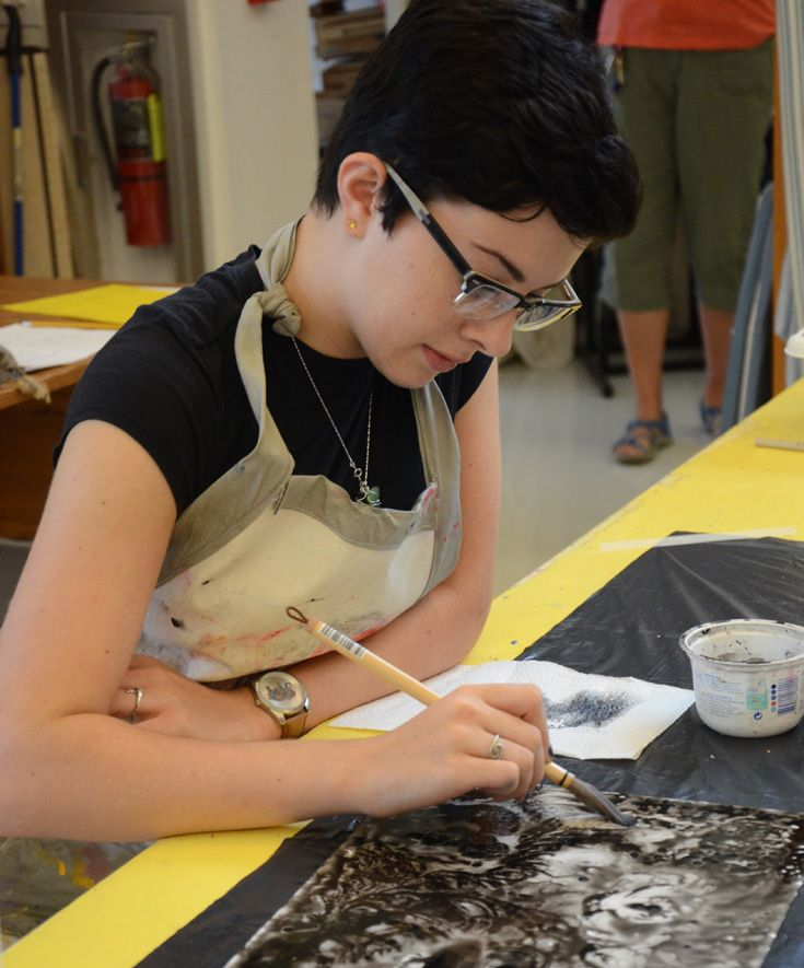 A student paints with ink over a wax resist.