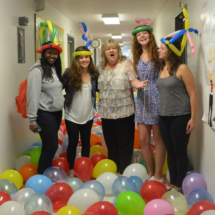 Seniors play a good-natured prank on Head of School Gina Borst by filling the second floor hallway with colorful balloons.