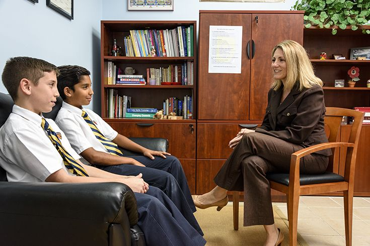 Director of School Counseling Teresa Gutierrez speaks to students in her office.