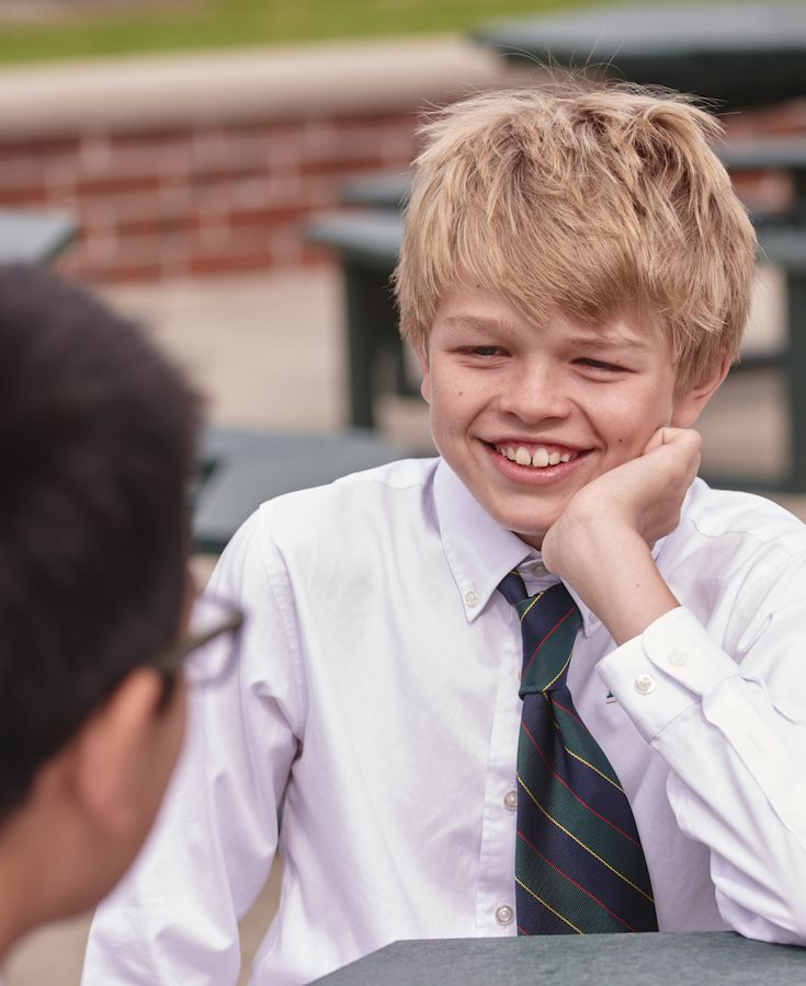 A Middle School student smiles brightly at their friend across the table. Rabun Gap is a private boarding school near the cities of Atlanta, Asheville, and Greenville.