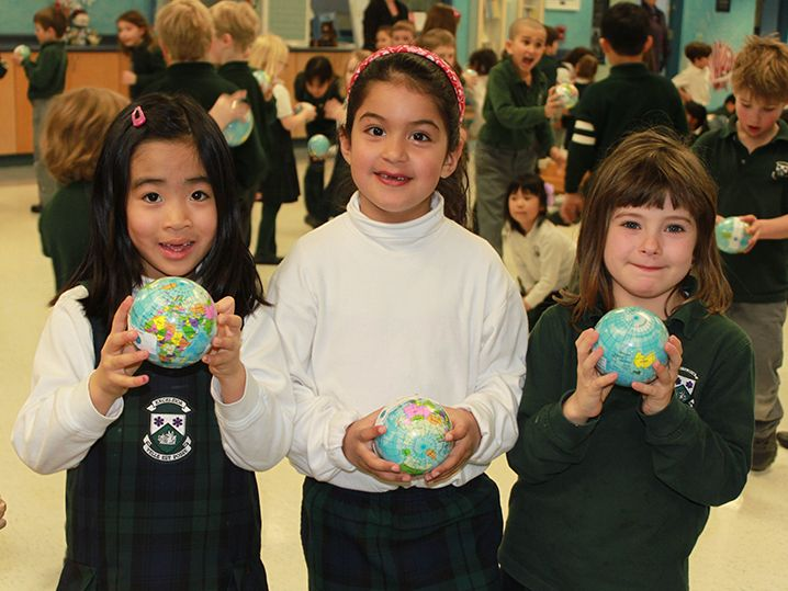 Students holding a Globe