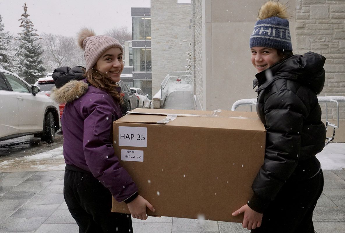 Two students wearing toques and winter jacketshold a large cardboard box labelled