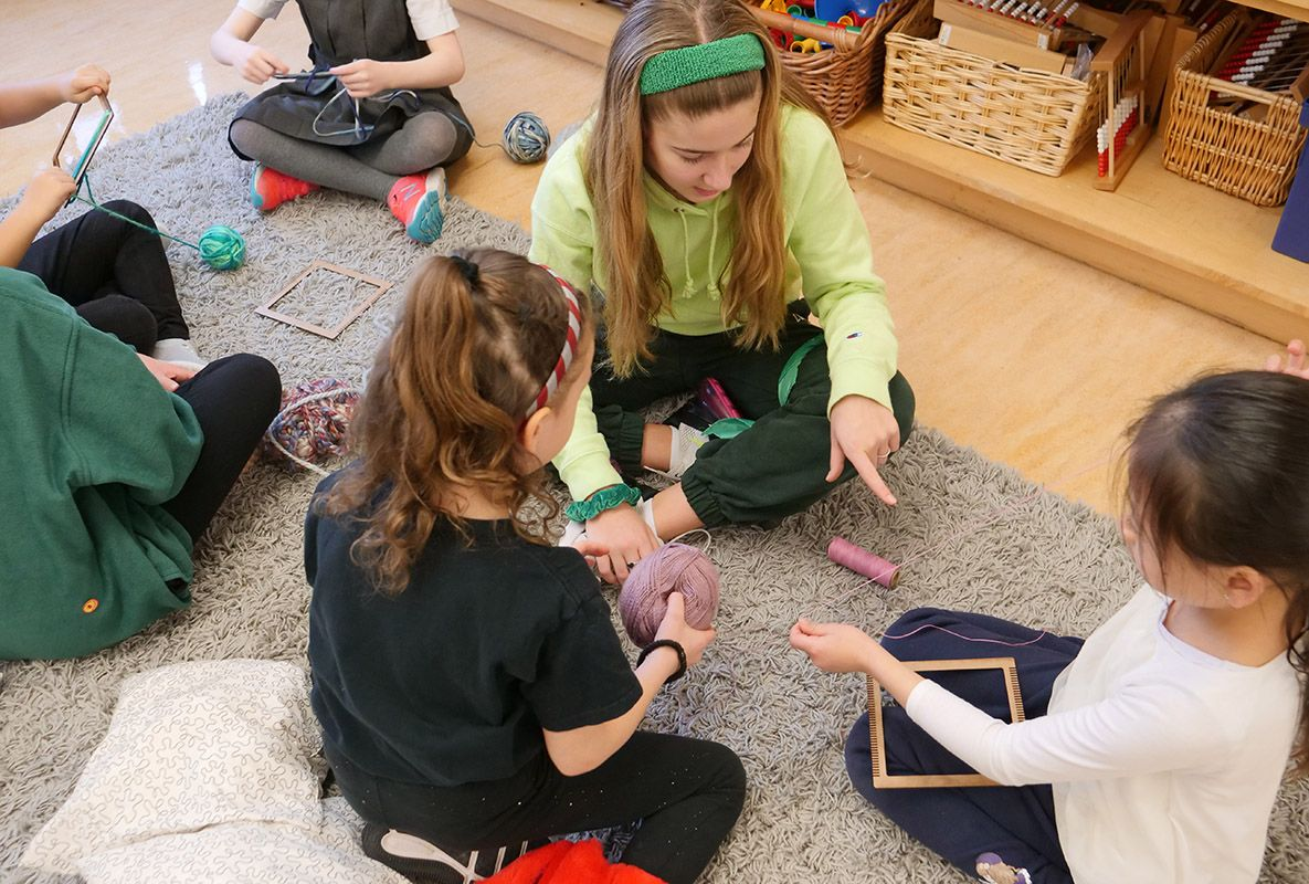 Older students sit on the floor and work on crafts with younger students