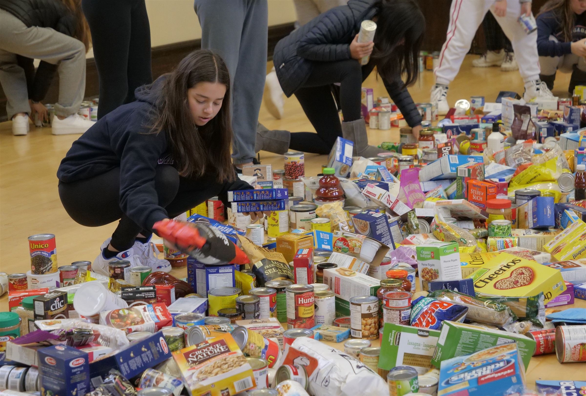 A student sorts through non-perishable food items that have been donated during a food drive