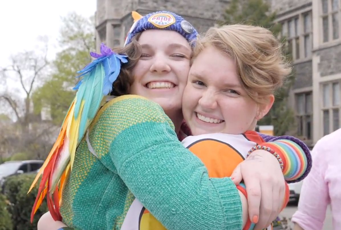 Two students wearing rainbow-coloured clothes embrace with big smiles on their faces
