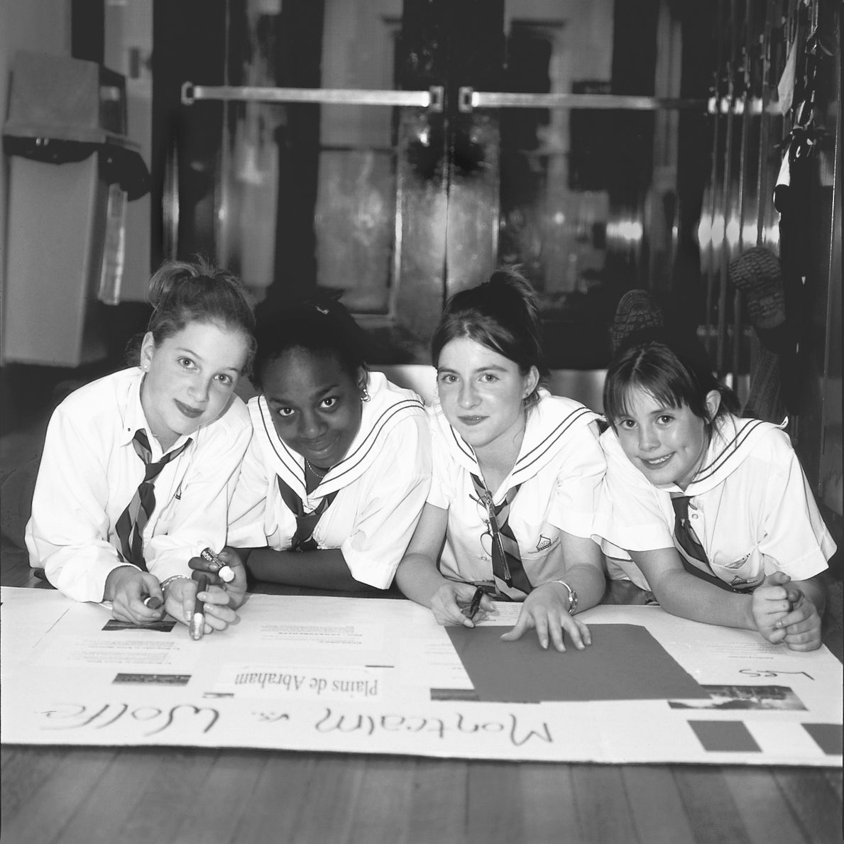 A black and white photo of a diverse group of students working on a poster together