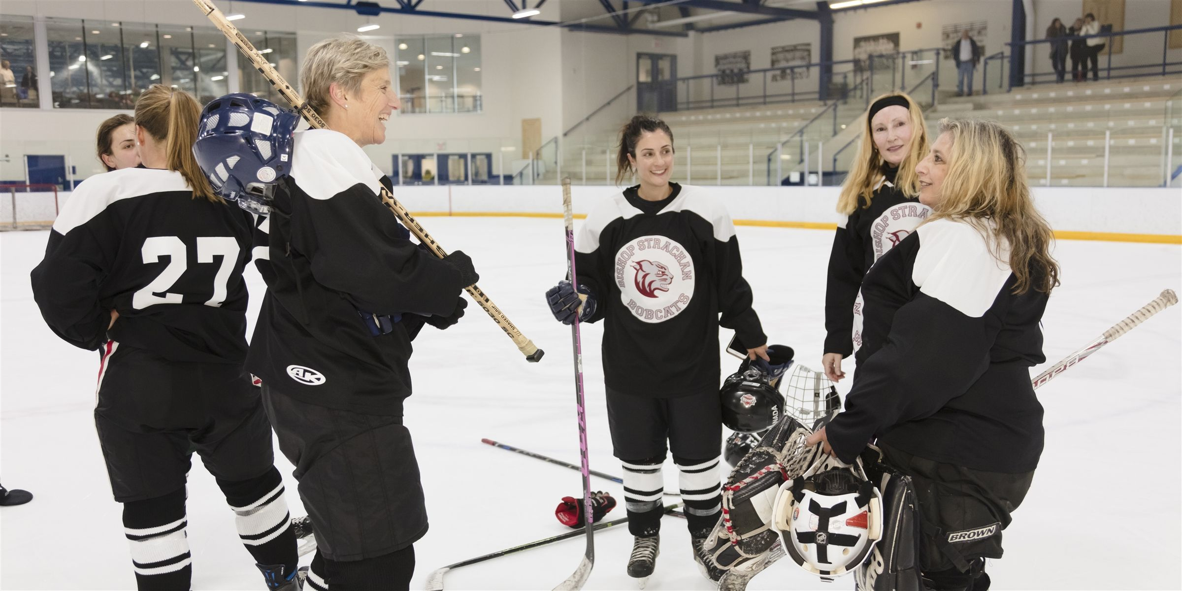 Alumnae in hockey gear on the ice