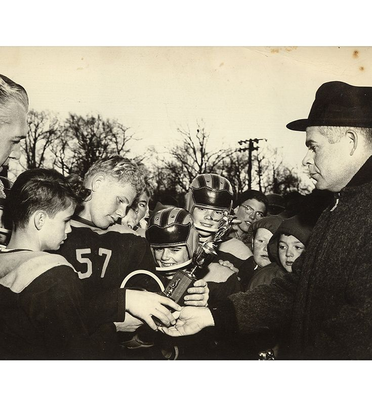 Rev. Francis Burns awards CYO football trophy.